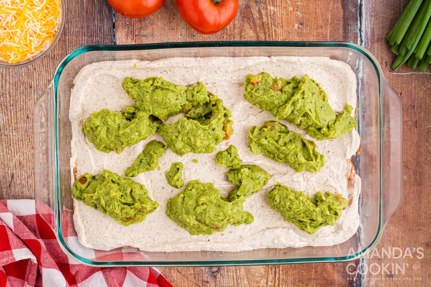 dollops of guacamole on top of sour cream and cream cheese in a dish