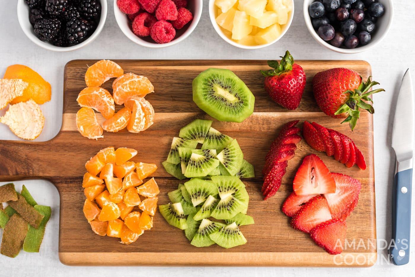 mandarin oranges, kiwi, and strawberries on cutting board