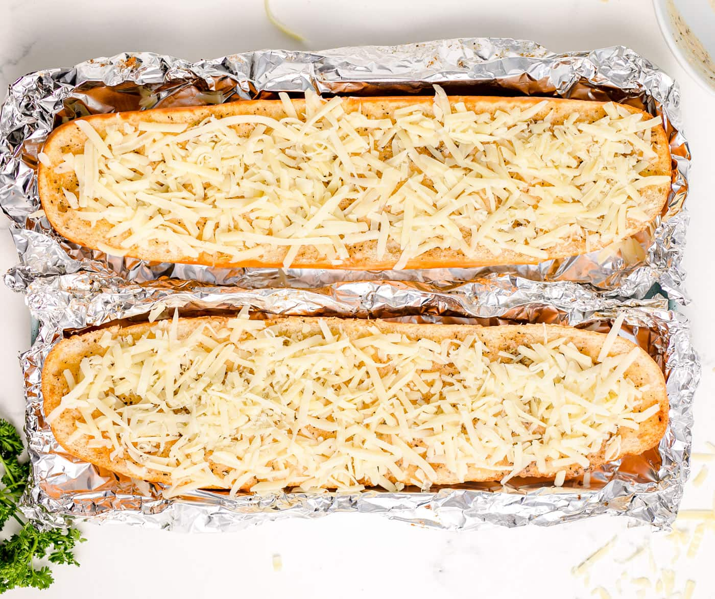 cheesy garlic bread on a pan with aluminum foil