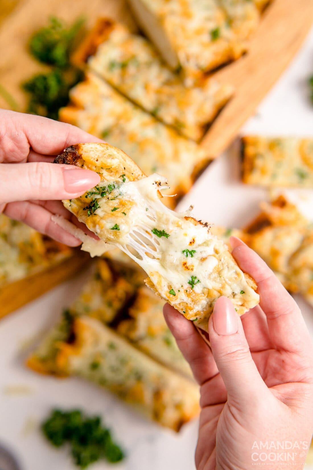 pulling a piece of Cheesy Garlic Bread apart