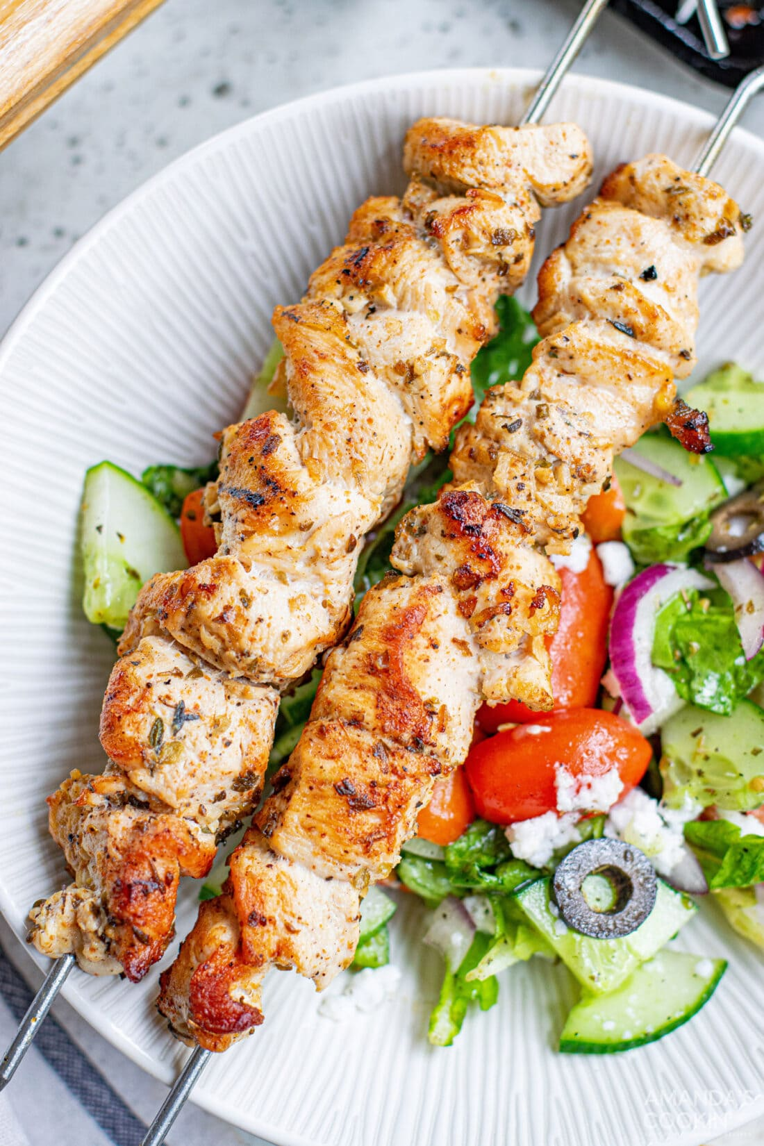 Greek Chicken Kabobs on a plate with salad