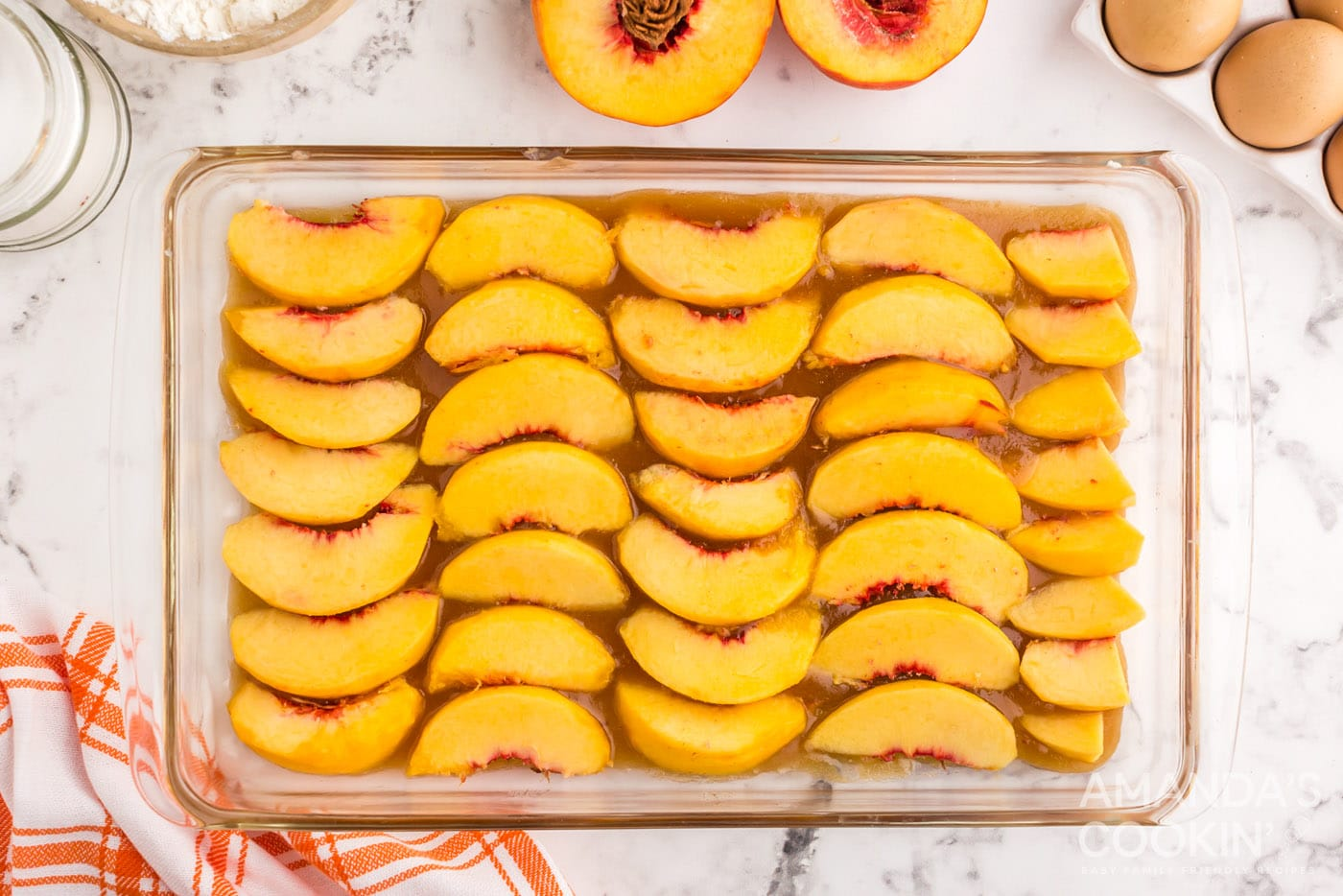 peach slices on top of butter and brown sugar mixture in a baking dish