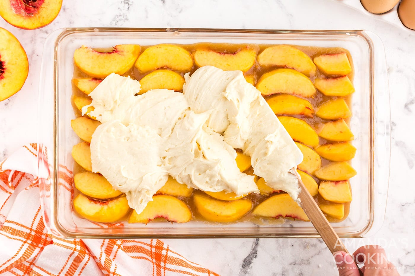 spread cake batter on top of peaches in a baking dish