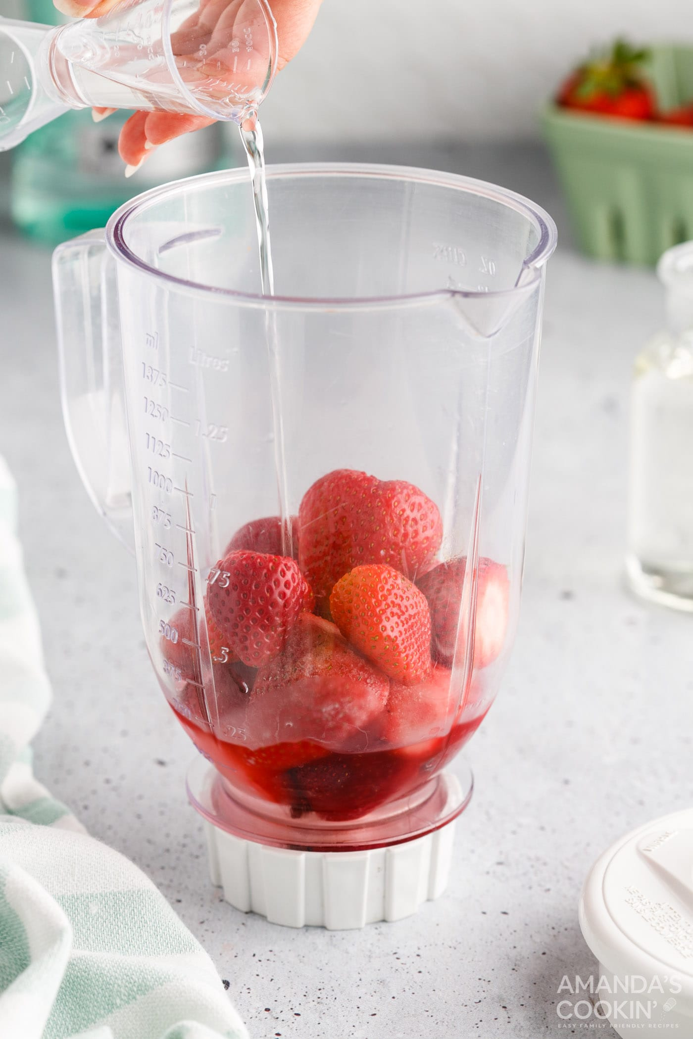 pouring simple syrup into strawberry daiquiri blender