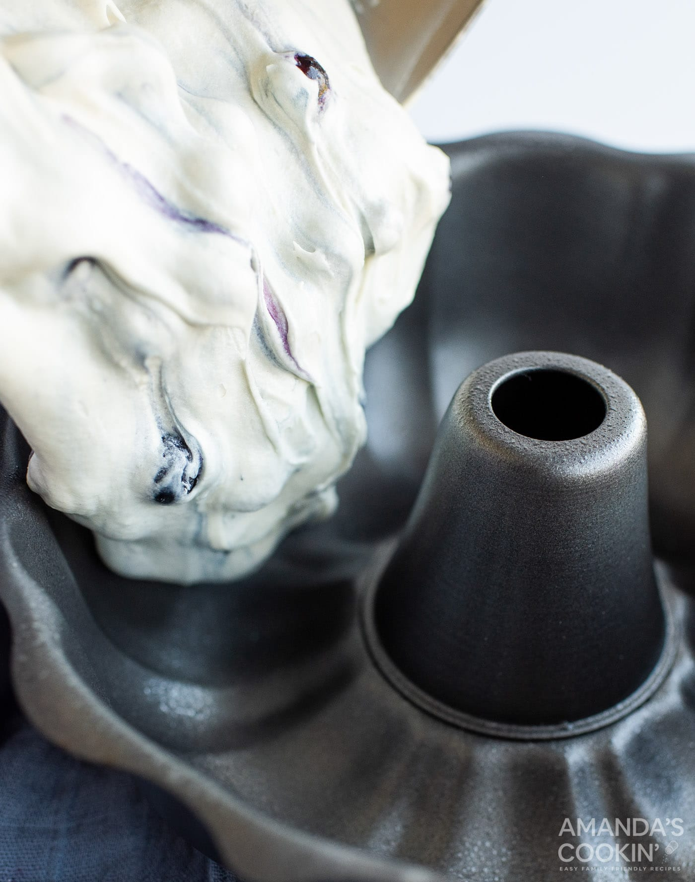 pouring blueberry cake batter into bundt pan