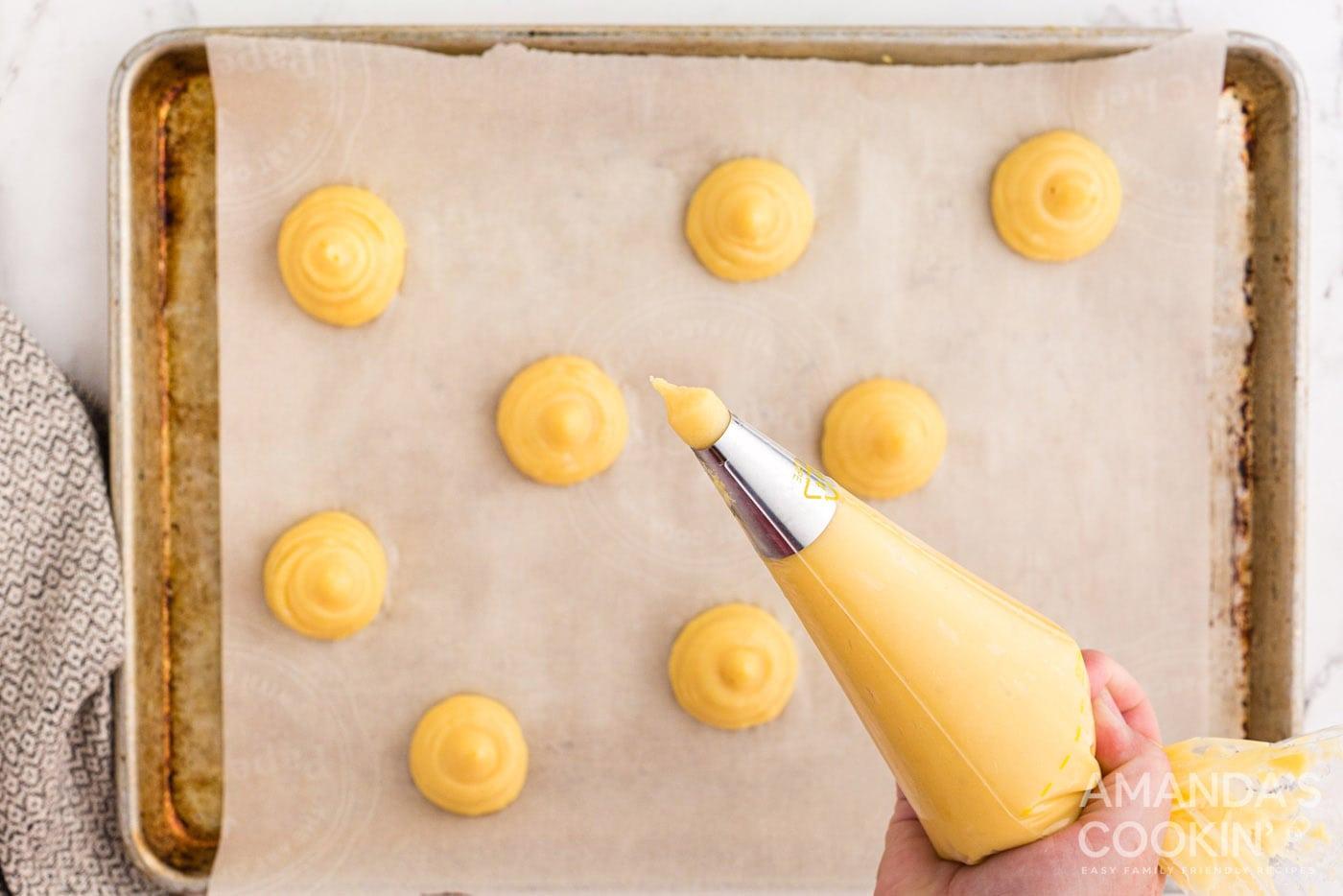 piping choux pastry dough onto baking sheet