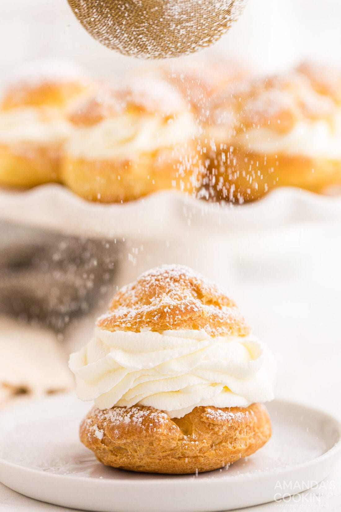 sifting powdered sugar on top of a Cream Puff