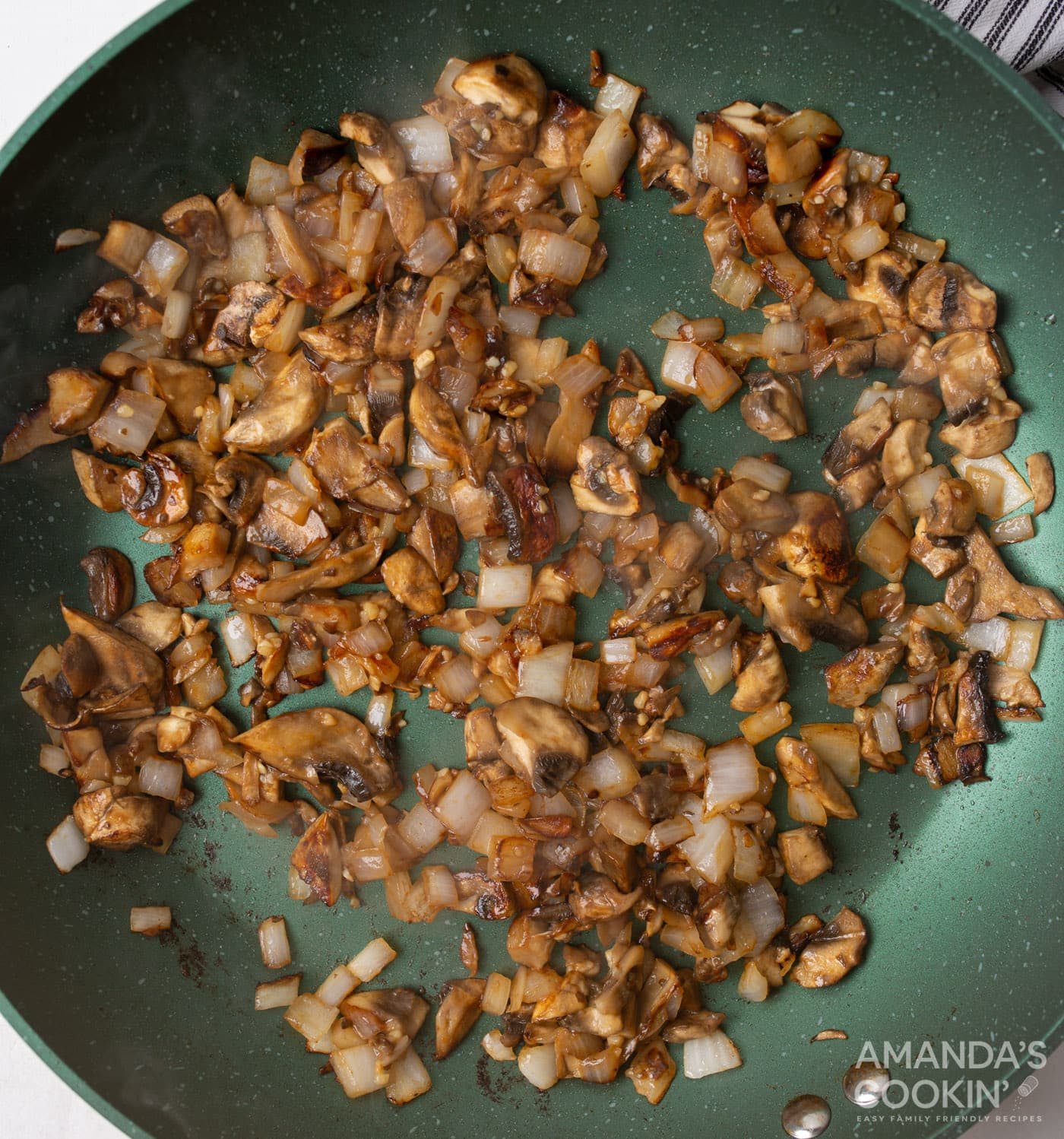 mushrooms and onion in a skillet with garlic