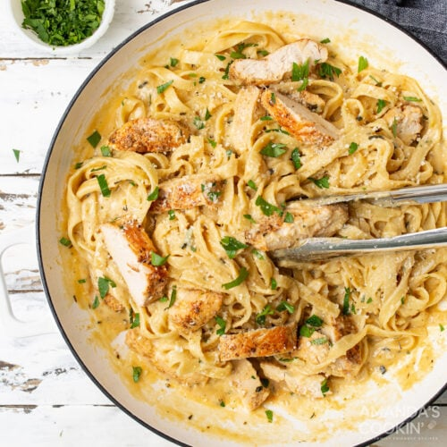 Chicken Alfredo in a serving dish with tongs