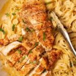 Chicken Alfredo with tongs