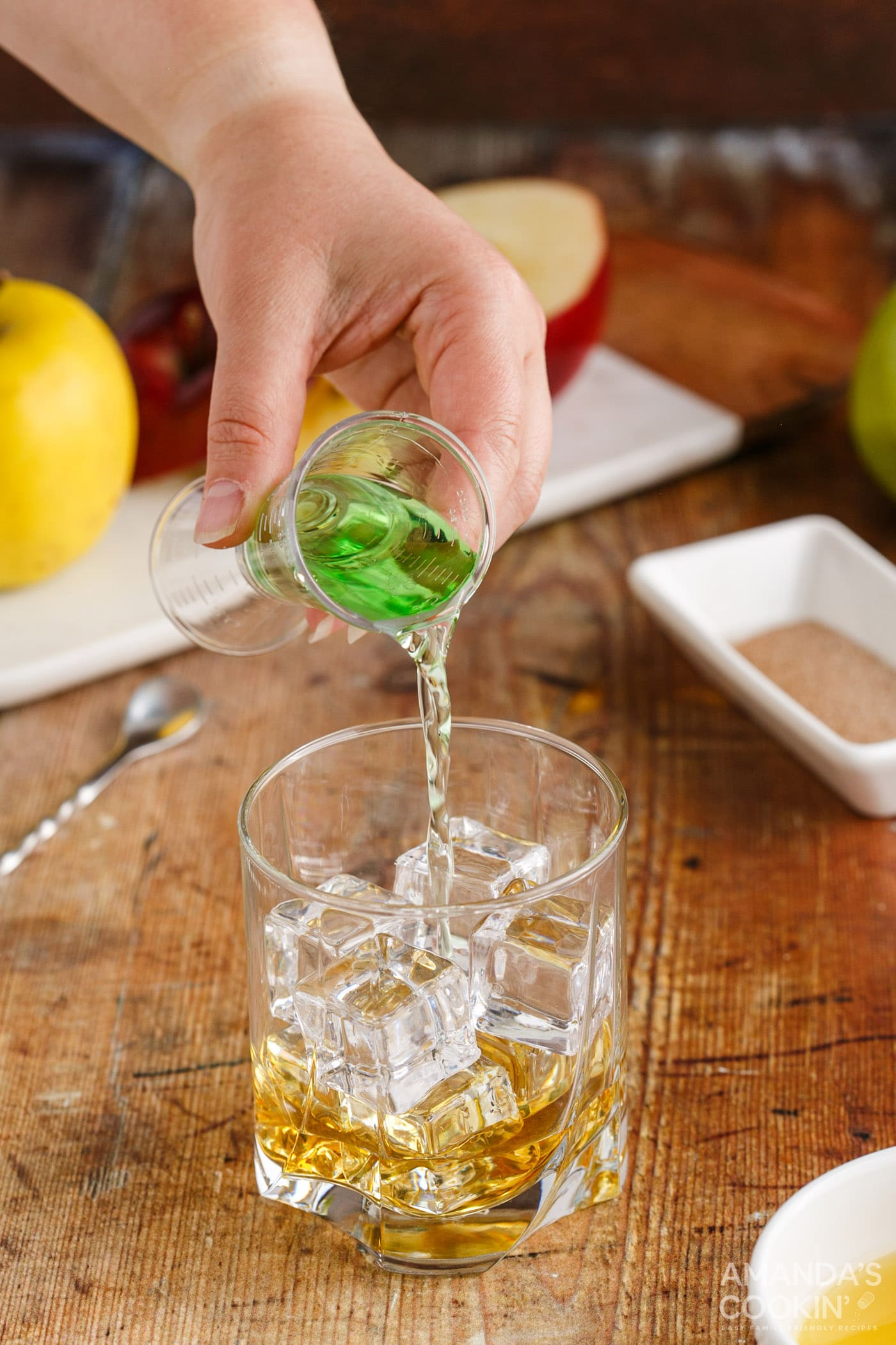 pouring apple pucker into a rock glass