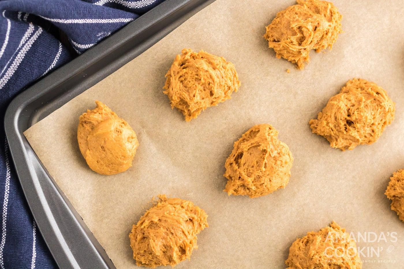 pumpkin cookie dough spooned onto a baking sheet