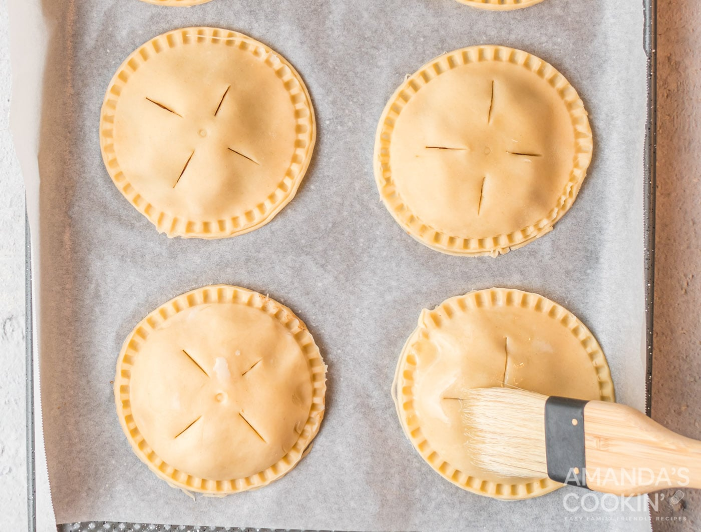 brushing apple hand pies with egg wash