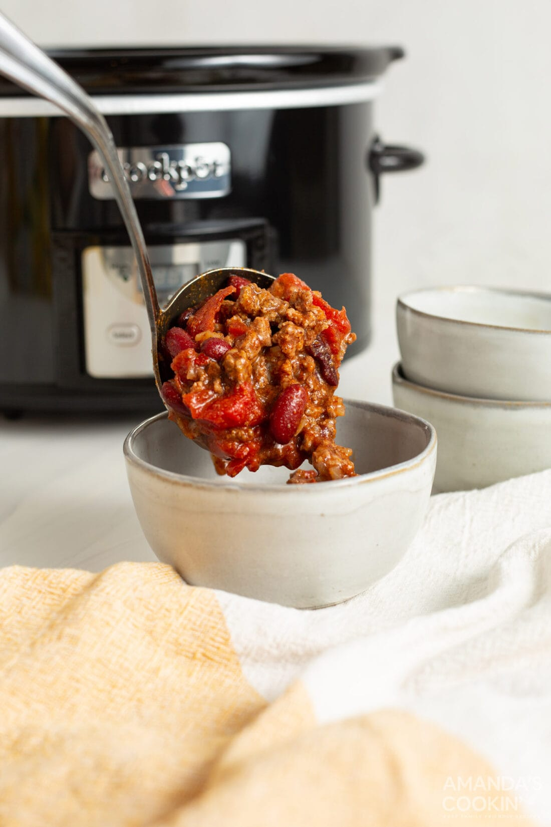 spooning Crockpot Chili into bowl