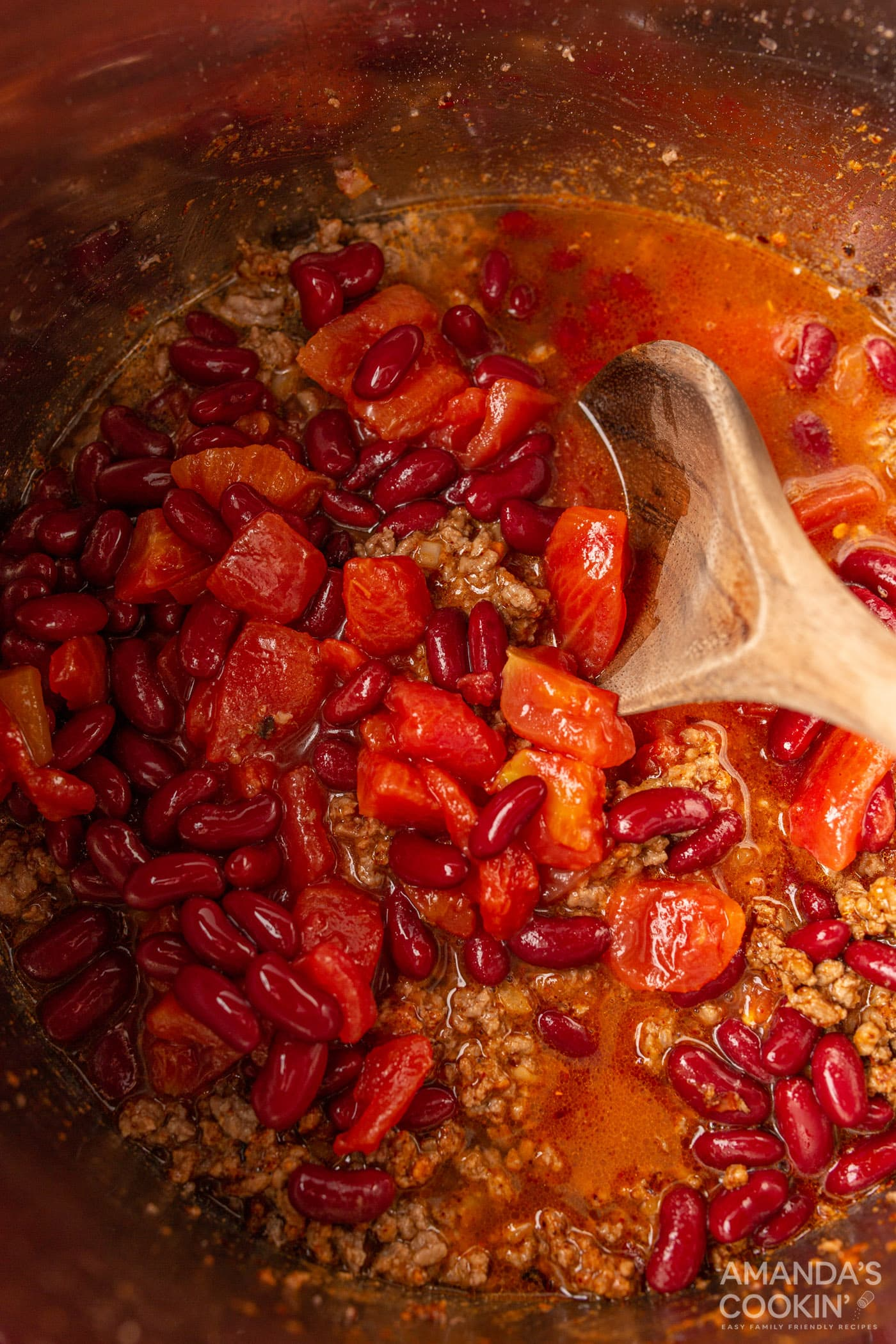 wooden spoon stirring tomatoes into chili