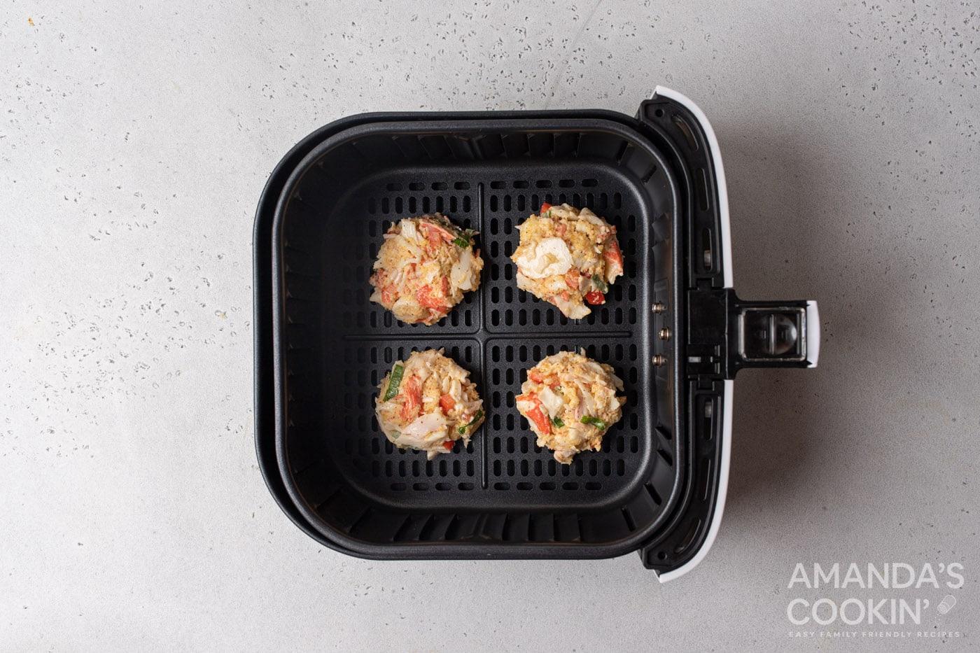 crab cake patties in an air fryer basket