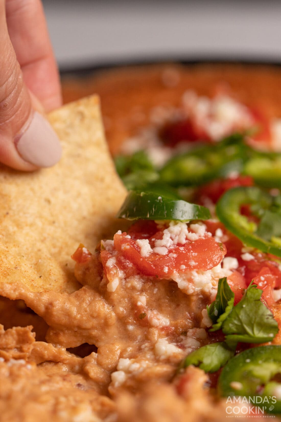scoping Bean Dip with nacho chip