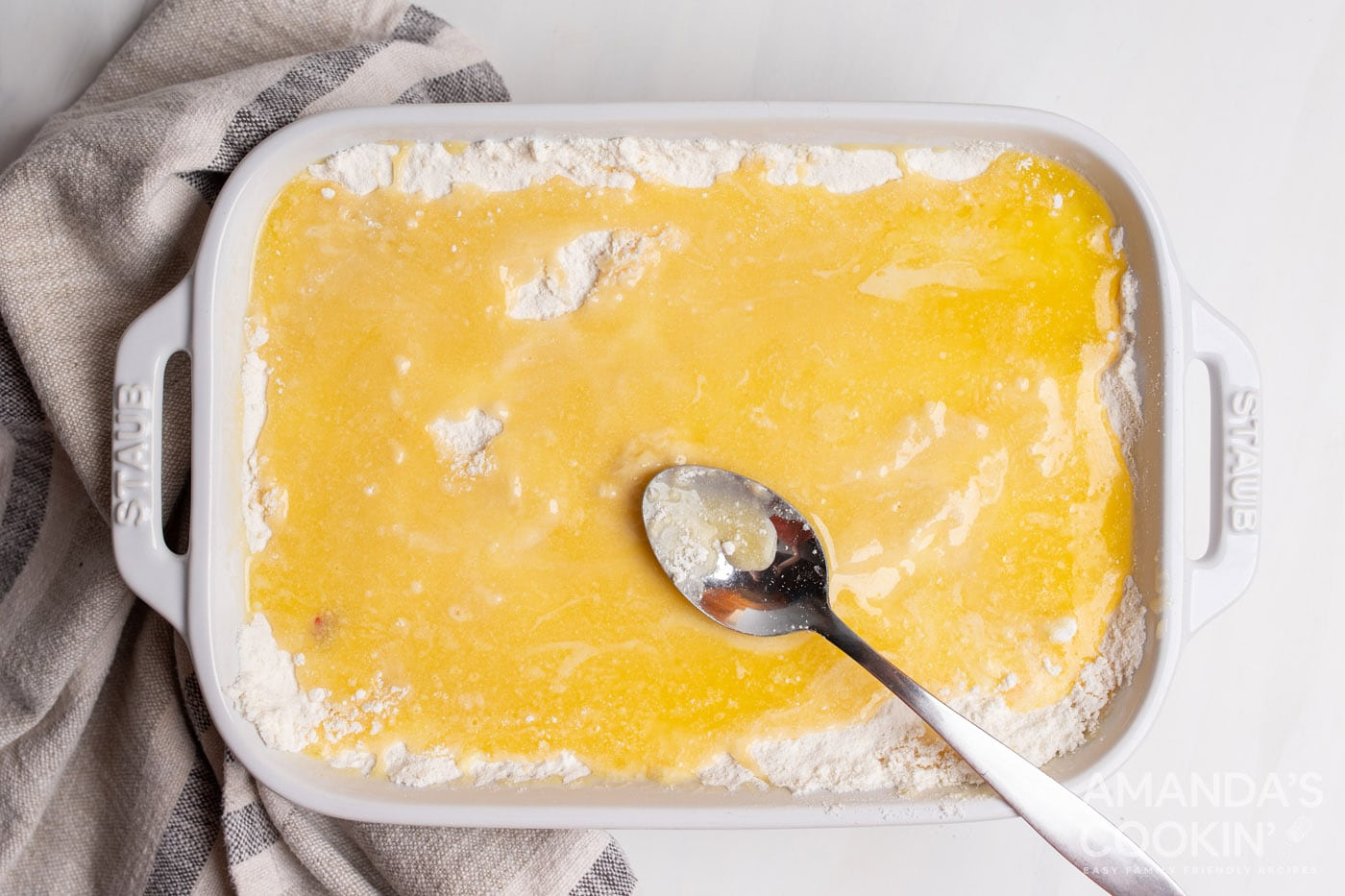 spooning butter over cake mix in a casserole dish