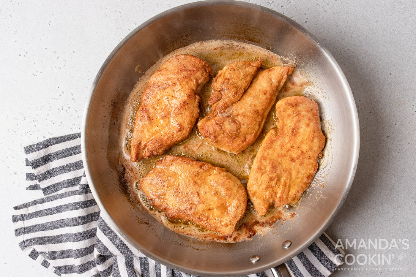 chicken cooking on a pan with butter and oil