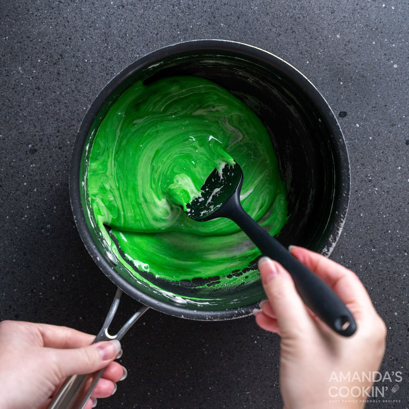 spoon stirring green food coloring into melted marshmallows