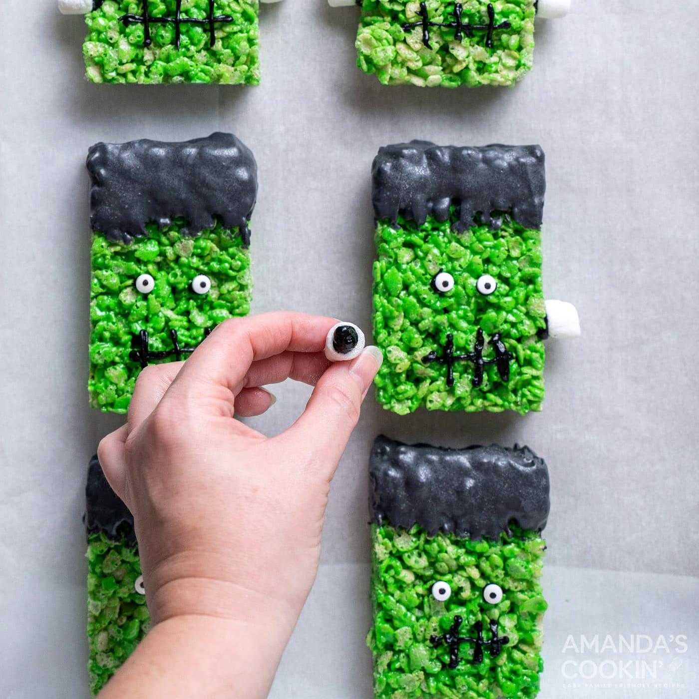 hand attaching mini marshmallows to frankenstein rice krispie treats