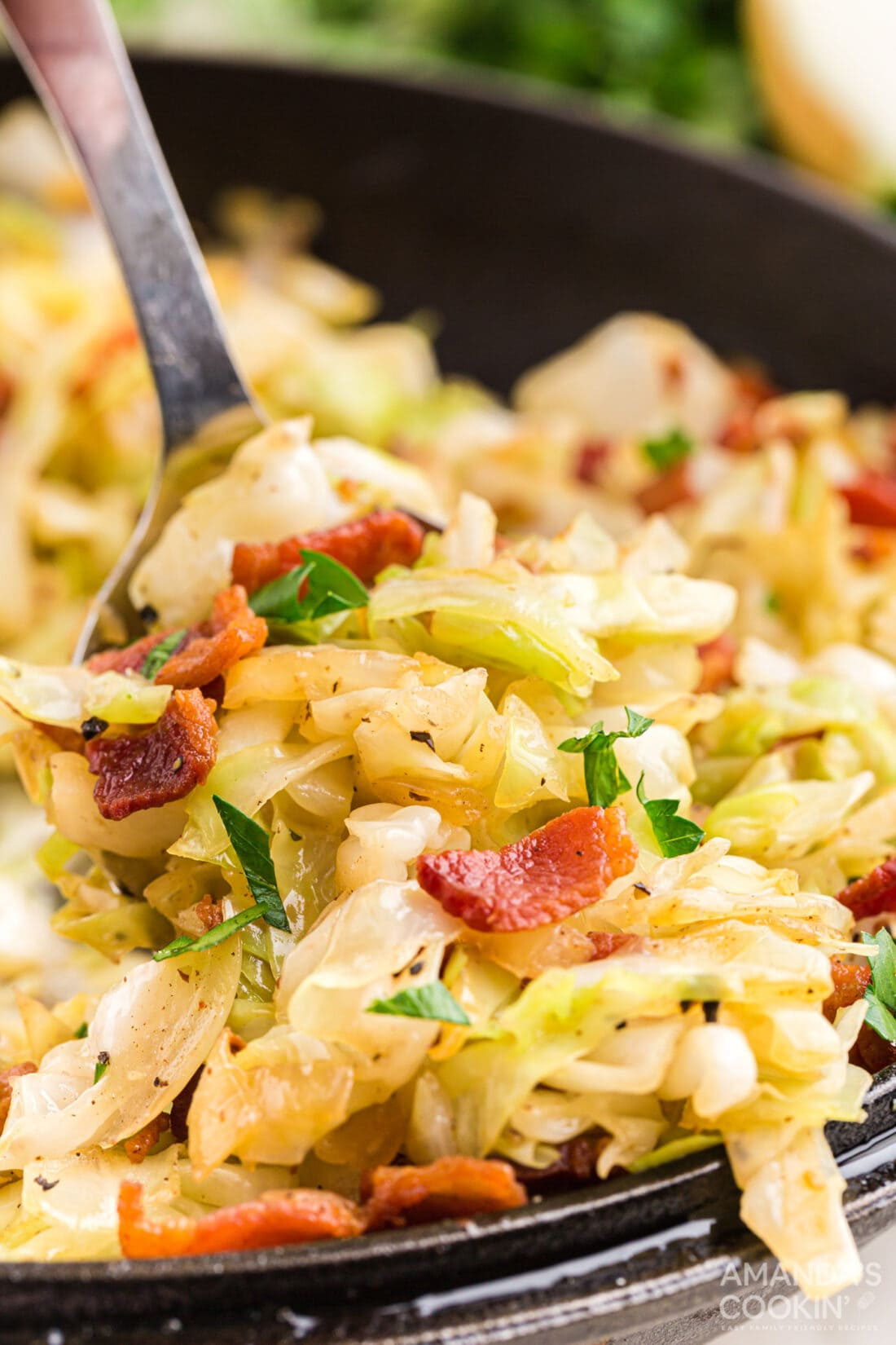 spooning out Fried Cabbage