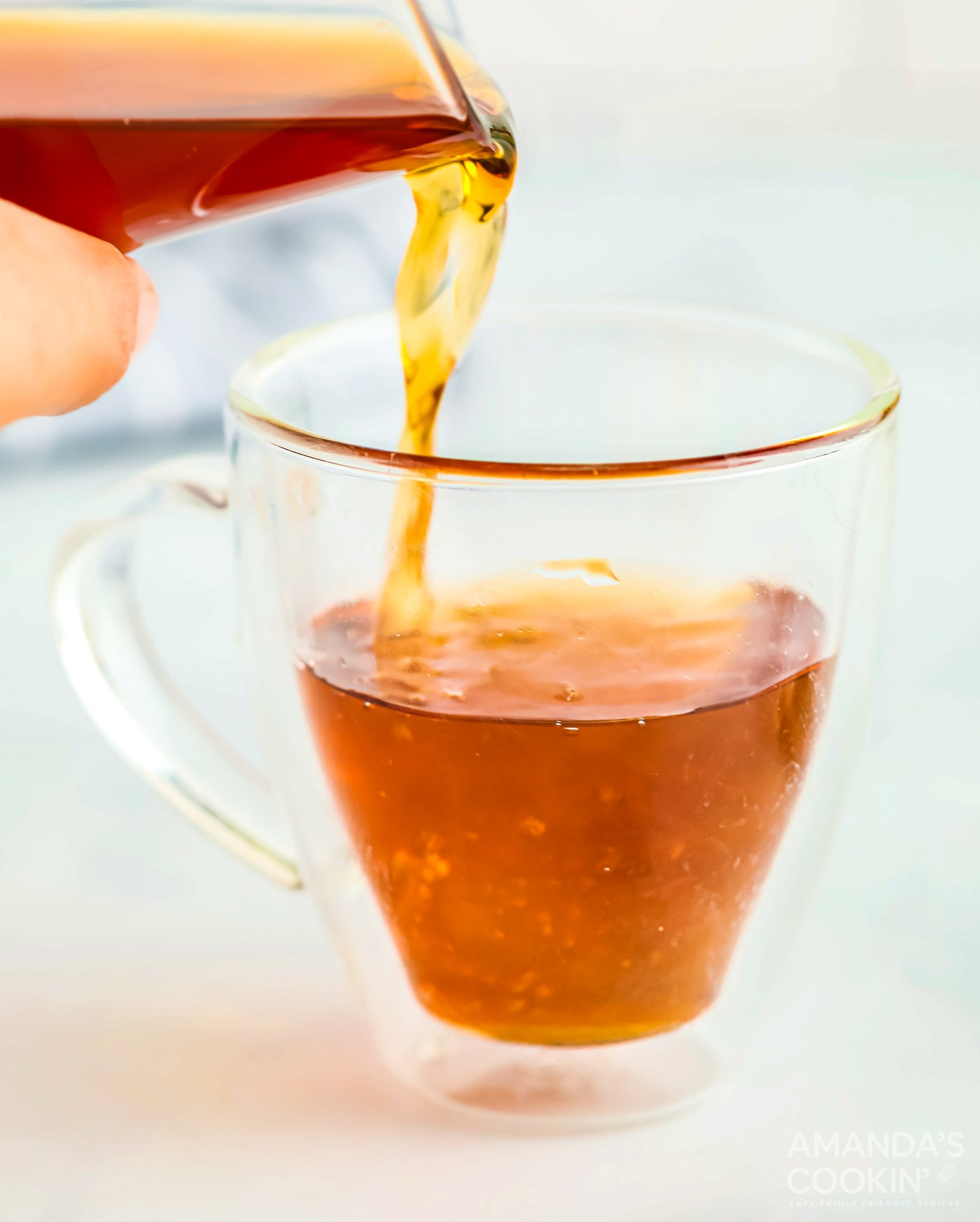pouring apple cider into a glass mug with whiskey and vodka