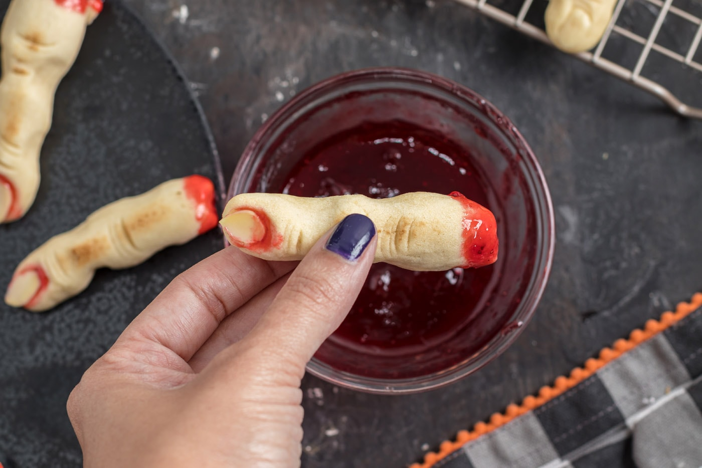 dipping witch finger cookies in jam