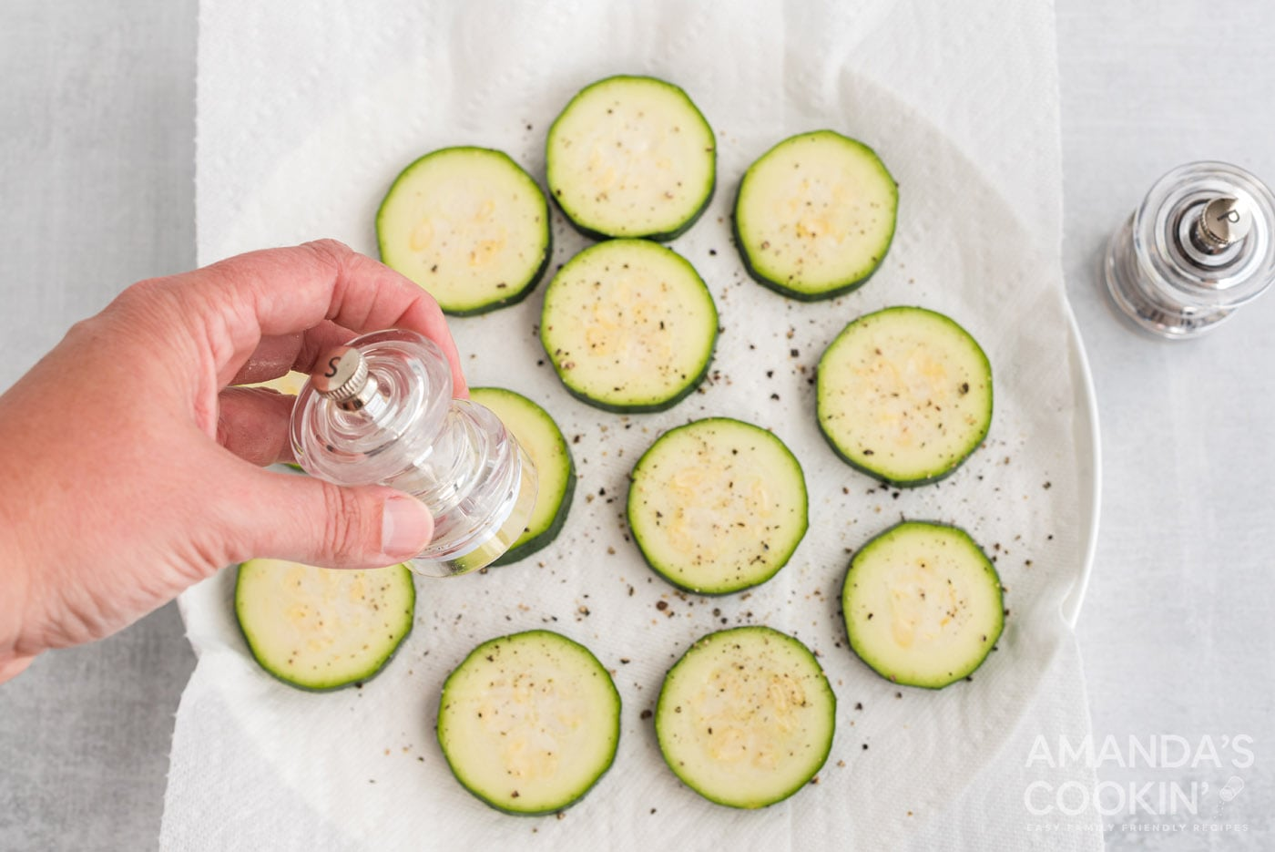 seasoning zucchini rounds with salt and pepper