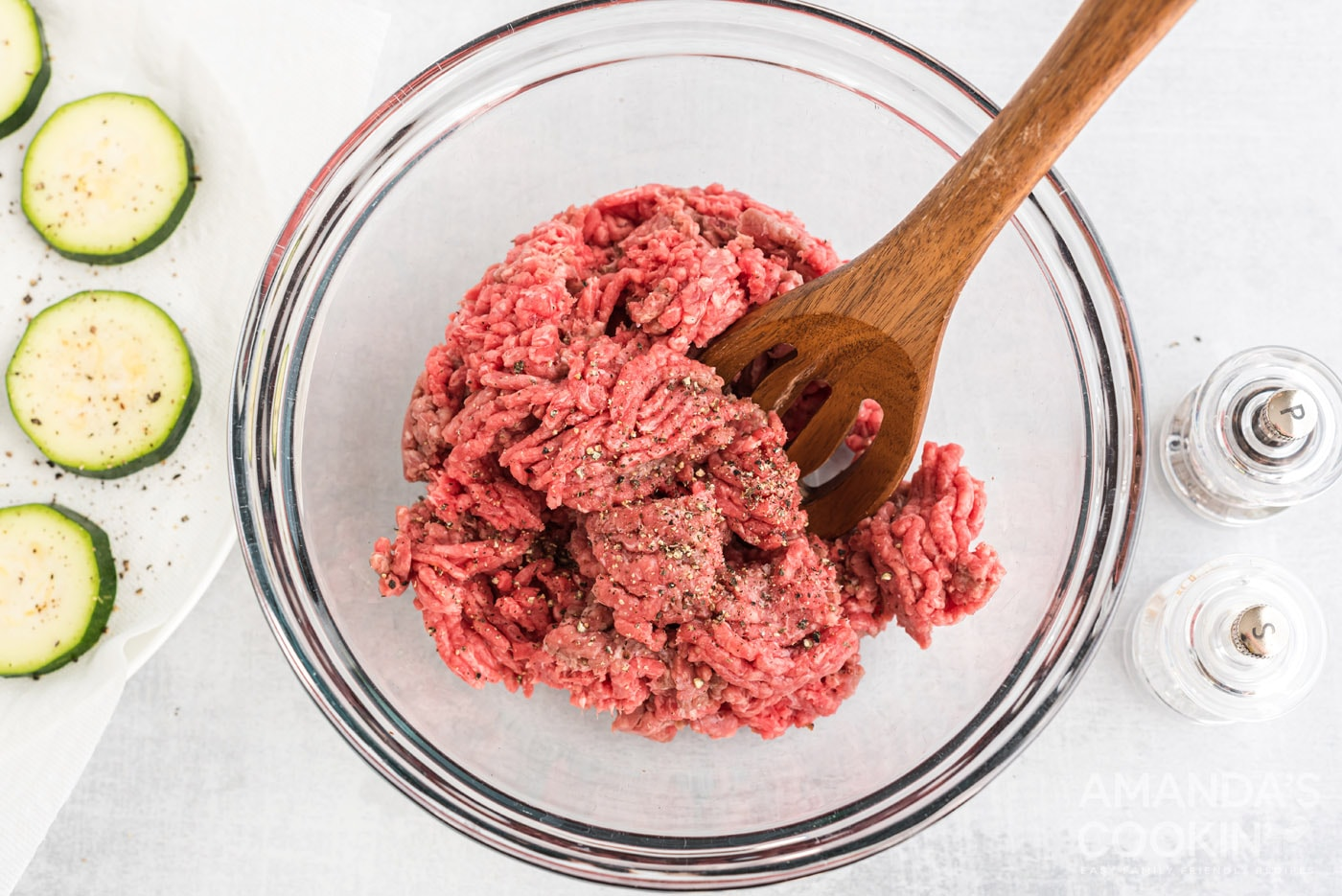 mixing spoon in a bowl of ground beef with salt and pepper