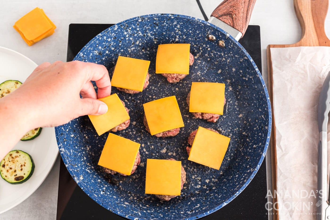 mini cheeseburgers in a skillet