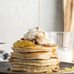 drizzling syrup onto apple pancakes