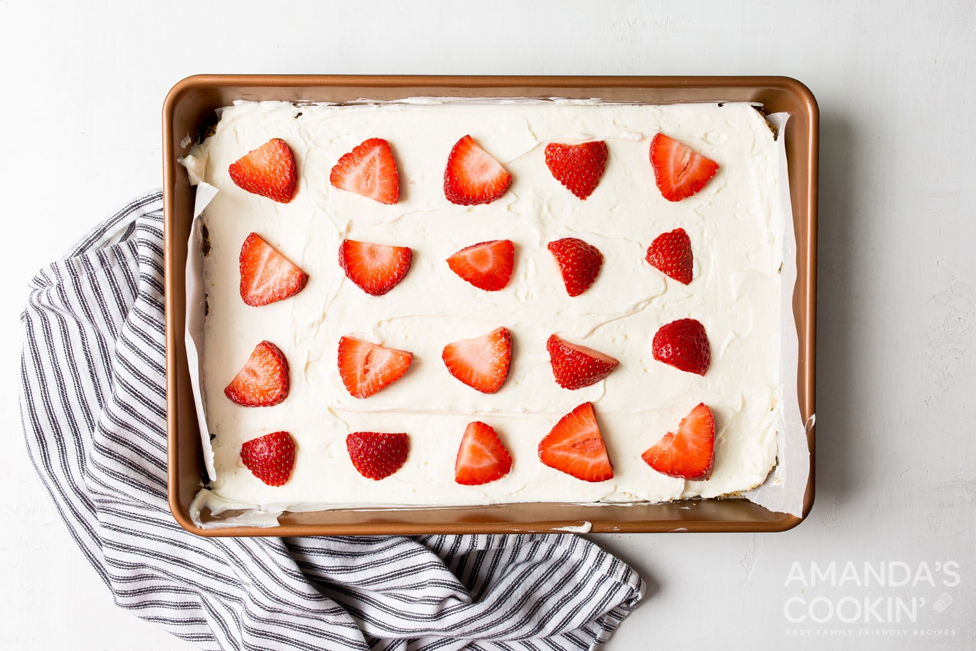 sliced strawberries on top of no bake cheesecake bars