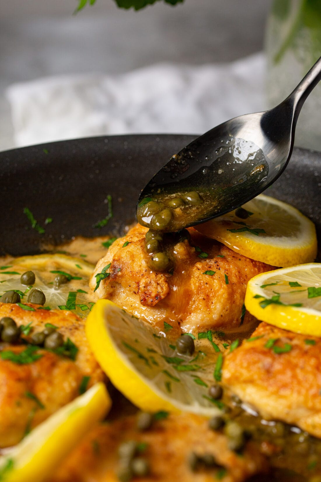 drizzling capers onto Chicken Piccata