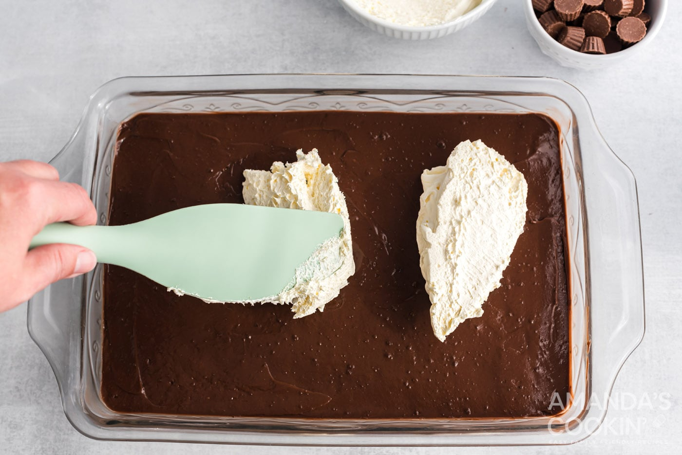 rubber spatula spreading whipped topping over chocolate pudding